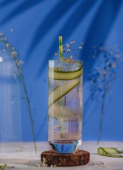 Вид сбоку испанского коктейля джин-тоник в бокале на деревянной подставке