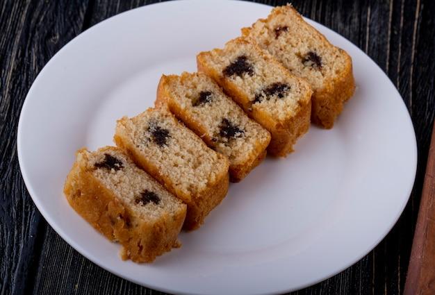 Вид сбоку кусочки бисквита с шоколадом на белой тарелке