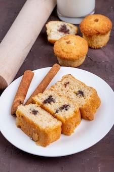Вид сбоку кусочки бисквита с палочки корицы на белой тарелке