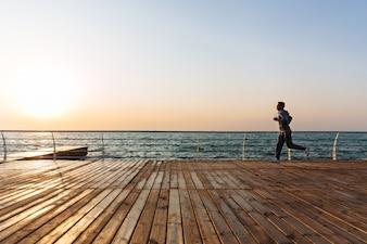 海岸近くの岸壁を走っている釣り好きな男の側面図