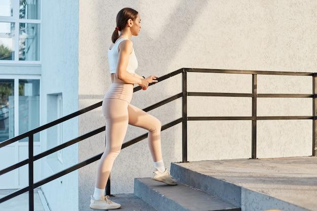 白いトップとベージュのレギンスを身に着けているスポーティで魅力的な黒髪の女性の側面図は、屋外で2階に上がり、まっすぐ前を見て、一人で運動します。