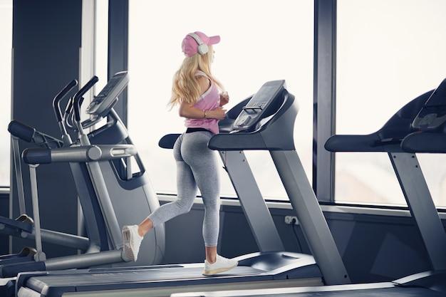 ジムのトレッドミルで運動しているピンクの帽子のスポーティなブロンドの女性の側面図