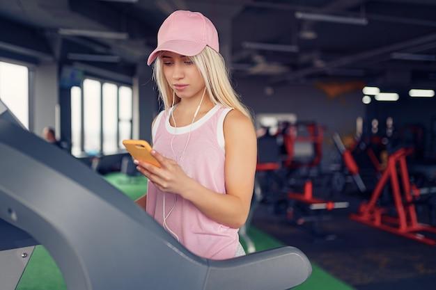 ジムでスマートフォンで音楽を選択してトレッドミルで運動する準備をしているピンクの帽子のスポーティなブロンドの女性の側面図