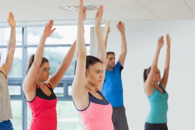 ヨガのクラスで手を上げるスポーティな人々の側面図