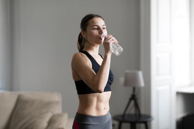 スポーティな女性は、水を飲むの側面図