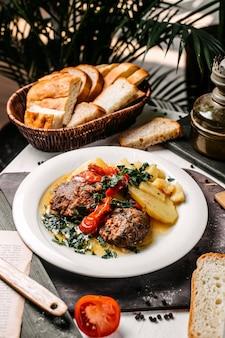 Вид сбоку тушеного мяса с картофелем и зеленью на белой тарелке