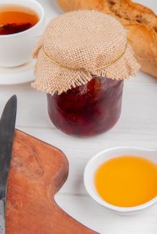 まな板の上のティーナイフと木製のテーブルのバゲットの溶かしたバターカップが付いている瓶のいちごジャムの側面図