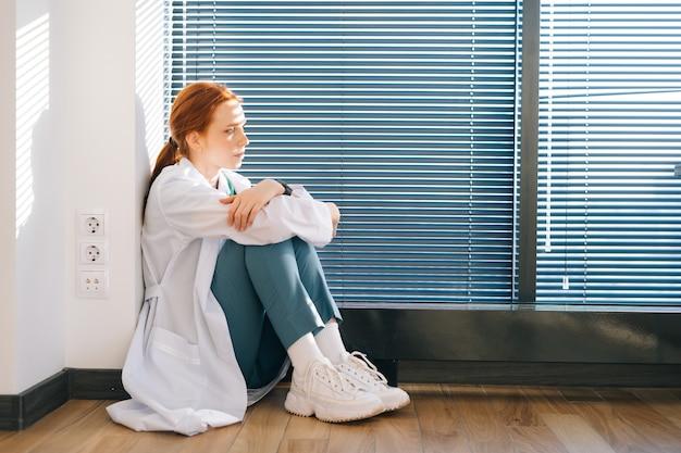 스트레스를 받고 화가 난 여성 의사의 옆모습은 화창한 날 창문 근처 바닥에 앉아 있는 전문적인 실수에 대해 걱정하고 있습니다. 흰 코트를 입은 우울한 슬픈 여자 의사는 팔을 머리에 감습니다.