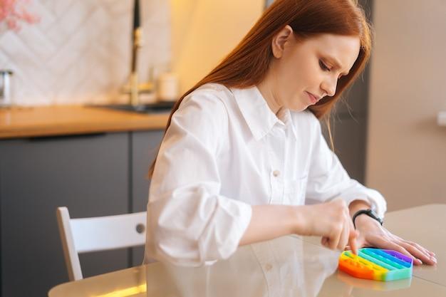 스트레스를 받는 젊은 여성이 간단한 방법으로 스트레스를 풀기 위해 감각 장난감을 가지고 노는 모습