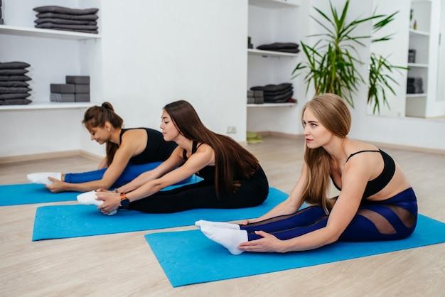 Вид сбоку растяжки на занятиях йогой в фитнес-группе молодых женщин