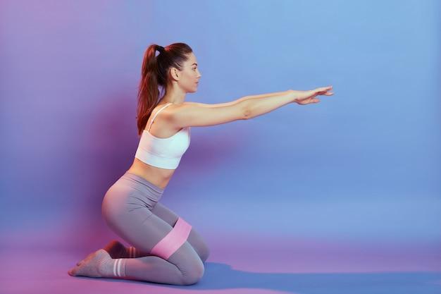Вид сбоку сильной и подтянутой спортивной молодой кавказской женщины в спортивной одежде