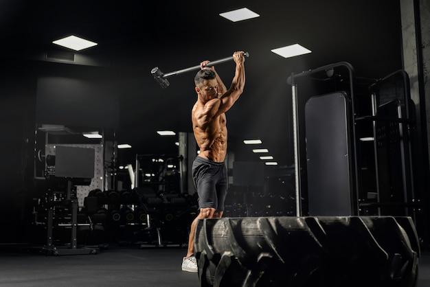쇠 망치로 거대한 타이어를 치는 강한 근육 질의 남자의 측면보기.