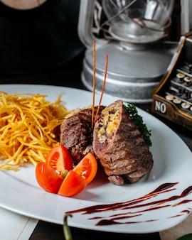 Вид сбоку фаршированная мясная котлета с овощами помидор и жареная картошка