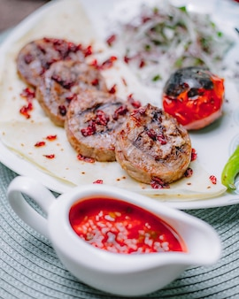Вид сбоку фаршированных грибами с сыром-курицей и орехами, украшенными барбарисом на лаваше, подается с жареными помидорами и луком с зеленью на тарелке