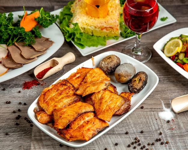 木製のテーブルの白い皿に焼きたてのジャガイモとチョウザメのケバブの側面図