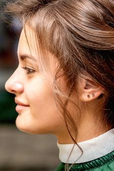 ビューティーサロンで美しい若い白人ブルネットの女性の髪のスタイリングの側面図