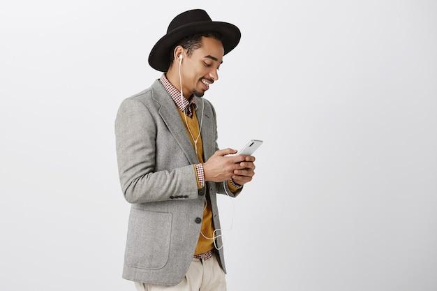 스마트 폰을 사용하고 이어폰에서 음악을 듣는 정장에 세련된 아프리카 계 미국인 남자의 측면보기