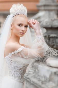 Вид сбоку стильной невесты в шикарном белом платье на улице, смотрящей в камеру