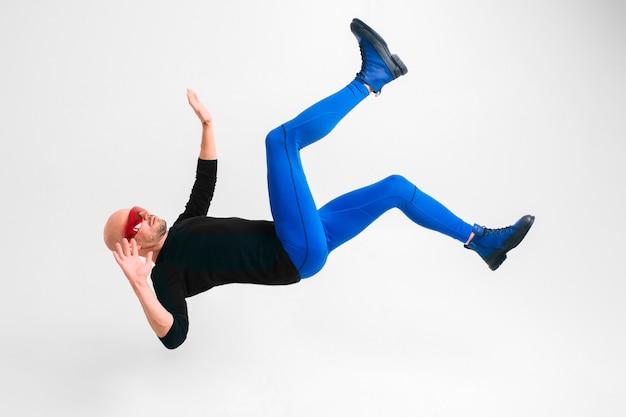 未来的な赤いメガネと空気で横になっている青いタイツでスタイリッシュな男の側面図