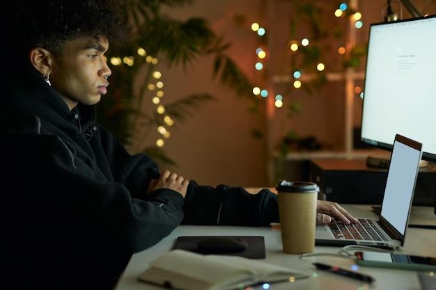 늦은 시간에 노트북 컴퓨터 작업을 하는 동안 모니터 화면을 보고 있는 세련된 젊은 남자의 측면