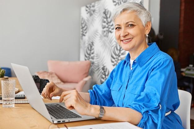 성공적인 성숙한 여성 블로거가 집에 앉아 노트북을 열고, 키보드를 사용하고, 심리학에 대한 새 기사를 넓은 자신감 미소로 작성하는 모습