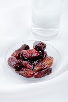 Вид сбоку сладких сушеных фиников в блюдце со стаканом воды на белом фоне