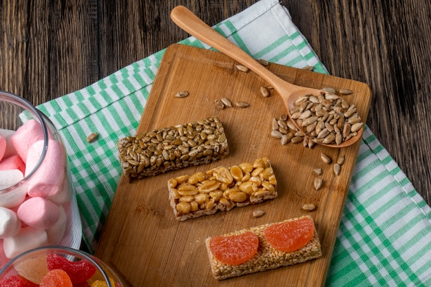 Вид сбоку сладких козинаков из семян подсолнечника кунжута и арахиса на деревянной доске и с красочными зефир в стеклянной банке на деревенском