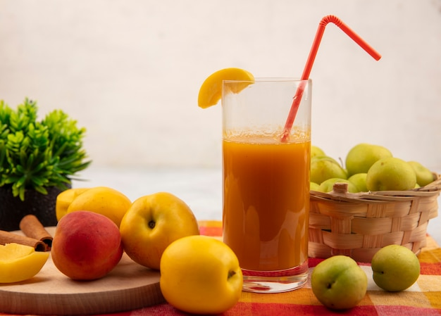 白い背景の上のチェックされたテーブルクロスのバケツに緑の桜の梅と桃ジュースとピンクがかったオレンジ色の桃と木製のキッチンボード上の甘い黄色の桃の側面図