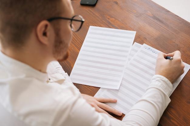 Вид сбоку на молодого талантливого композитора в стильных очках, пишущего музыкальные ноты