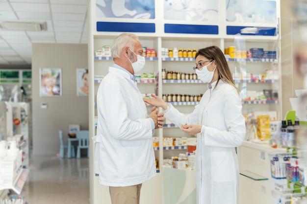 두 약사와 코로나 바이러스 간의 대화 측면보기. 은퇴하기 전에 약사는 젊은 약사에게 약국에서 일하는 것에 대해 가르칩니다. 그들은 유니폼과 안면 마스크를 쓰고