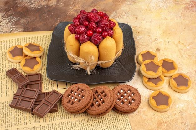 混合色のテーブルの茶色のプレートにおいしいケーキのさまざまなビスケットの側面図