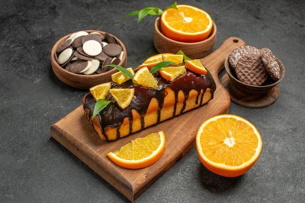 Вид сбоку вкусных тортов нарезанных апельсинов с печеньем на разделочной доске на темном столе