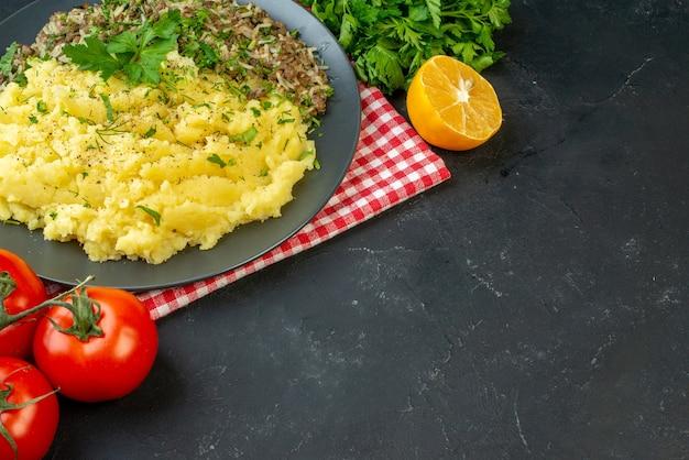 Вид сбоку вкусного ужина с мясным пюре на тарелке и помидорами со стеблями упавшего перца бутылки масла на черном фоне со свободным пространством