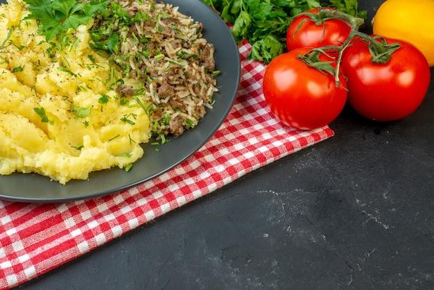 Вид сбоку вкусного ужина с мясным пюре на тарелке на красном полосатом полотенце и помидорами со стеблями на черном фоне