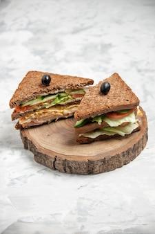 스테인드 흰색 표면에 나무 커팅 보드에 올리브로 장식 된 검은 빵과 함께 맛있는 샌드위치의 측면보기