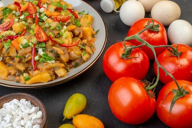 黒の背景に茎の卵の落ちたオイルボトルとおいしいビーガンミールフレッシュトマトの側面図