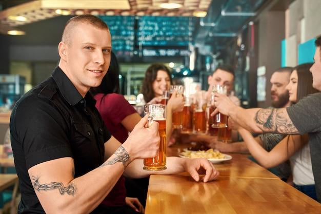 맥주 잔을 유지하고 카메라를보고 술집에서 포즈를 취하는 검은 셔츠에 문신을 한 남자의 측면보기. 강한 젊은이 웃 고 술집에서 친구와 함께 맛있는 에일을 마시는. 훈과 여가의 개념.