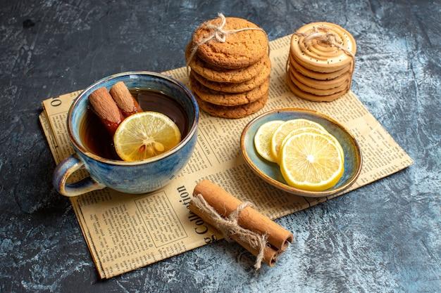 Вид сбоку на время чая с сложенными вкусным печеньем, корицей и лимоном на старой газете на темном фоне