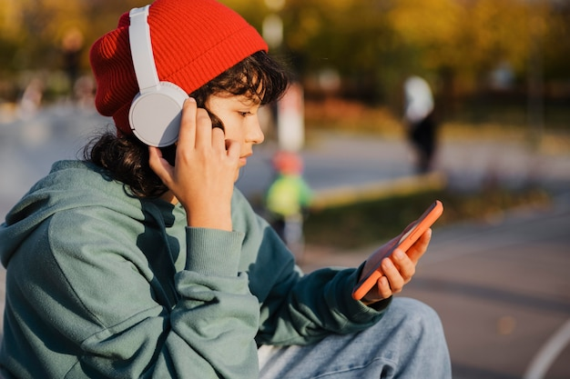 Вид сбоку на подростка, слушающего музыку в наушниках во время использования смартфона