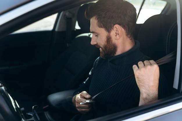 Вид сбоку на кавказского молодого бородатого человека в машине, пристегивающей ремни безопасности перед вождением. уверенный в себе парень катается на работе. запасное фото
