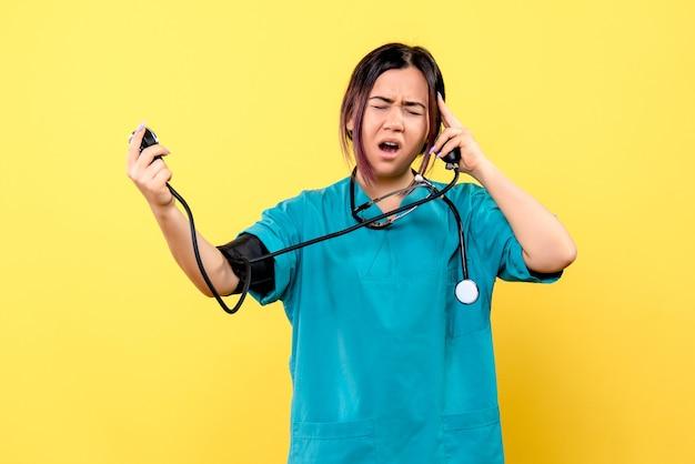 Вид сбоку у врача болит голова, измеряет давление