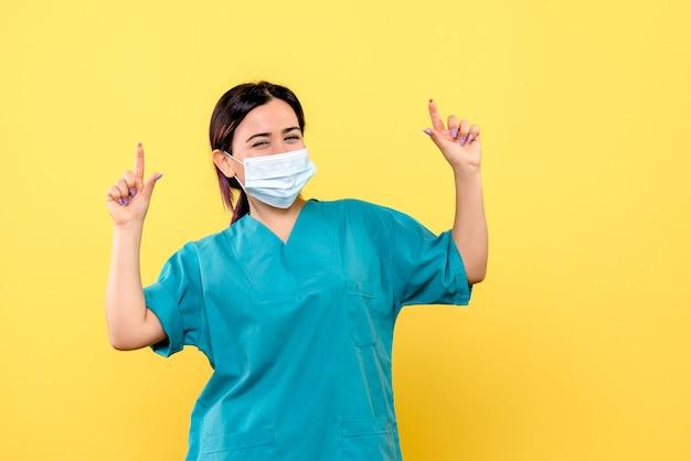 마스크를 쓴 의사의 측면은 코로나 바이러스로 환자를 치료하는 방법을 알고 있습니다.