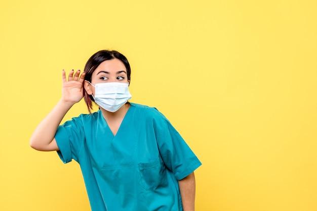 마스크를 쓴 의사의 측면은 코로나 바이러스 환자의 불만을 경청합니다.