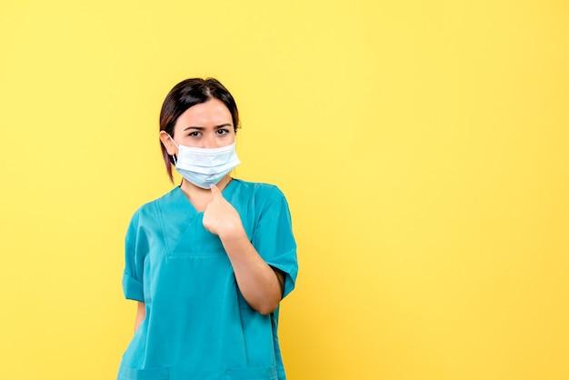 파란색 의료 제복을 입은 의사의 측면보기는 마스크를 가리 킵니다.