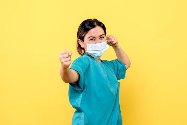 마스크를 쓴 의사의 측면은 코 비드 증상을 치료하는 방법을 알고 있습니다.