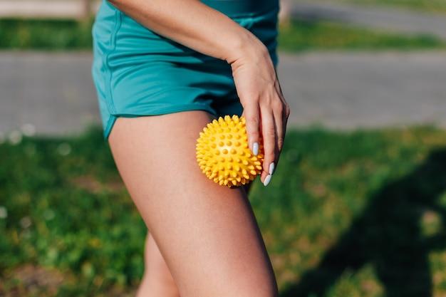 여름에 공원에서 뾰족한 공으로 엉덩이 마사지를 하는 젊은 여성의 얇은 운동 신체의 측면 보기.