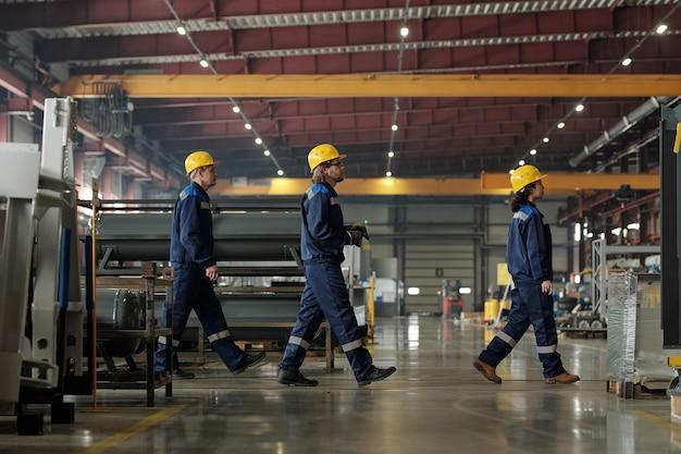 다른 작업장에 가거나 점심을 먹기 위해 앞으로 나아가는 현대 공장 또는 산업 공장의 세 엔지니어의 측면 보기