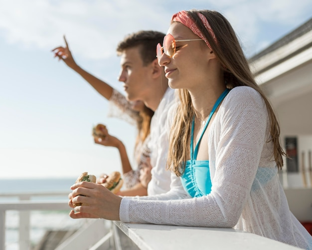 Вид сбоку трех друзей на открытом воздухе, вместе наслаждающихся гамбургерами
