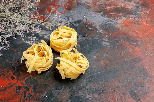 混合色のテーブルの3つの未調理のスパゲッティ部分の側面図