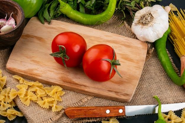 Вид сбоку помидоров на разделочной доске с чесноком, острым перцем, ножом и мятой на бежевой салфетке